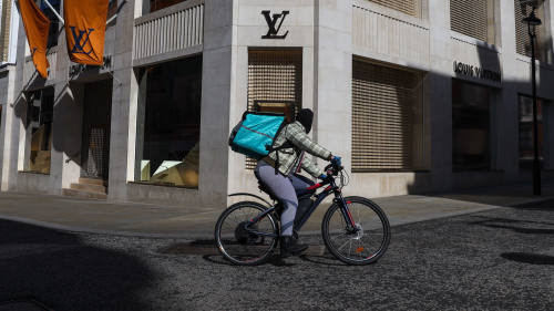A food delivery courier passes a closed Louis Vuitton store, operated by LVMH Moet Hennessy Louis Vuitton SE, in central London, U.K., on Tuesday, March 24, 2020. The U.K. is in lockdown after Boris Johnson ordered sweeping measures to stop people leaving their homes