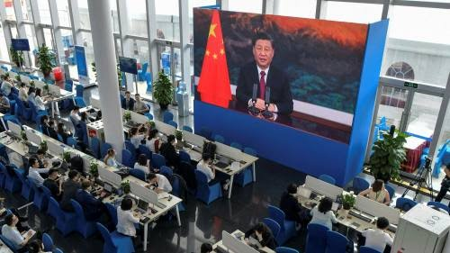 Journalists watch a screen showing China's president Xi Jinping delivering a speech during the opening of the Boao Forum for Asia in April