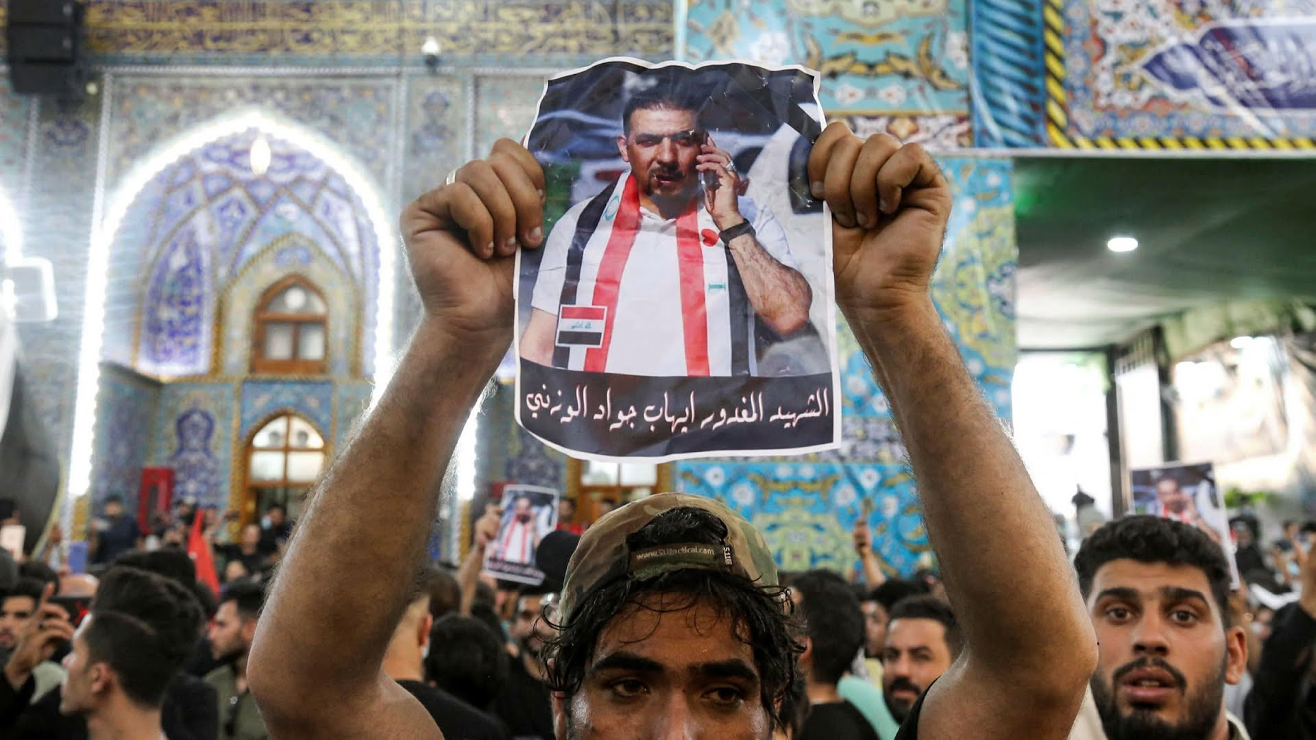 A mourner holds a poster of assassinated Iraqi activist Ihab al-Wazni