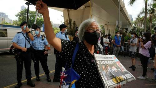 A pro-democracy activist holding a copy of Apple Daily newspaper outside a court in Hong Kong